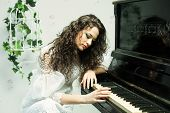 Romantic brunette girl playing piano close up shot poster