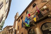 Buonconvento (Siena Tuscany Italy) - Historic buildings with clock tower and colorful flags poster