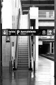 Railway station with signposting and escalators black and white poster