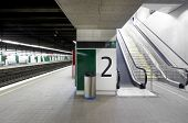 Railway station with signposting platforms and escalators horizontal poster