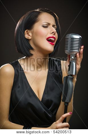 Half-length portrait of female singer with closed eyes wearing black evening dress and keeping microphone on grey background. Concept of music and retro fashion