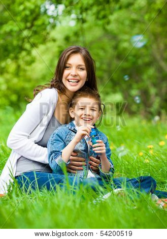 Mum and son with book sitting on green grass in park. Concept of happy family relations and carefree leisure time