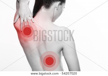 View from behind of a young woman with shoulder and back pain stretching back her hand to touch her shoulder blade with red selective colour to the injured areas