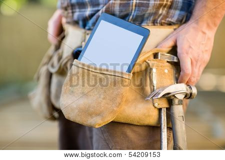 Closeup of digital tablet and hammer in carpenter's tool belt outdoors