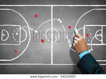 Close up image of human hand drawing football tactic plan poster