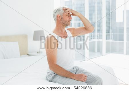 Side view of a mature man suffering from headache in bed at home