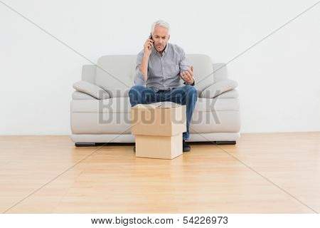 Mature man using cell pone while sitting on sofa with boxes in a new house