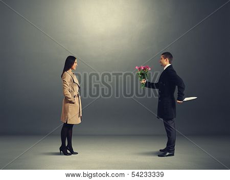 young couple on the date. crafty man holding flowers and looking at young beautiful woman