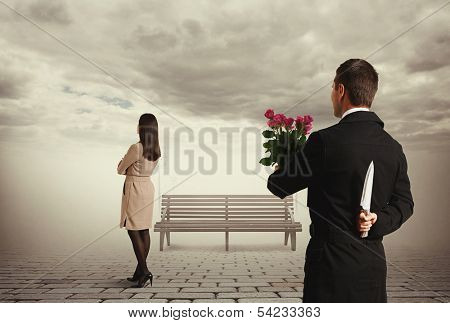 perfidious man holding flowers and knife behind back