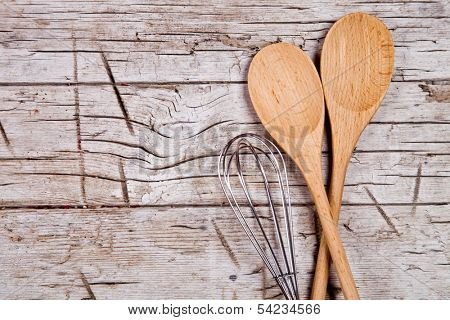 spoons and wire whisk on rustic wooden background