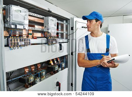 Young adult electrician builder engineer inspecting electric counter equipment in distribution fuse box