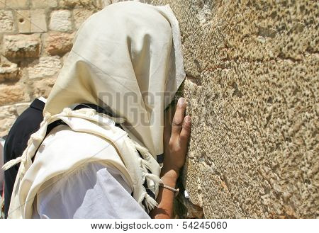 JERUSALEM - AUGUST 19: Unidentified man with head covered by tallit prays at Western Wall - the most important religious site and Holy place place for Judaism in Jerusalem, Israel on August 19, 2004.