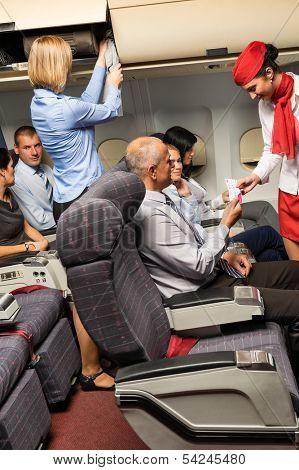 Flight attendant check passenger tickets in plane cabin