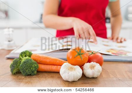 Close-up mid section of a woman with recipe book and vegetables in the kitchen at home