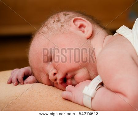 Portrait of infant resting on mother moments after birth at hospital