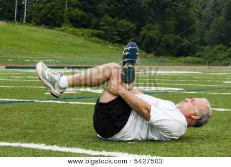 Middle Age Man Stretching And Exercising On Sports Field