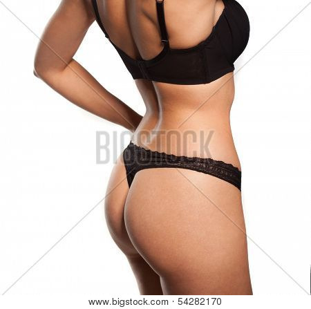 Close up view of the shapely curvaceous body of a sexy tanned young woman in black lingerie standing with her hands to her hips, torso view on white