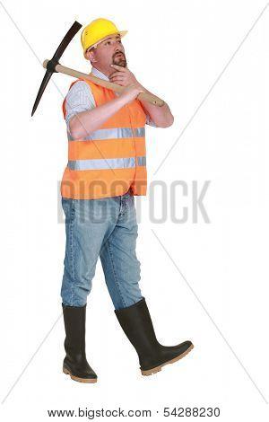 Contemplative labourer holding a pickaxe