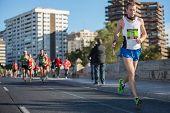 VALENCIA - NOVEMBER 17: Ando (number 205) participates in Valencias marathon on November 17, 2013 in Valencia, Spain poster