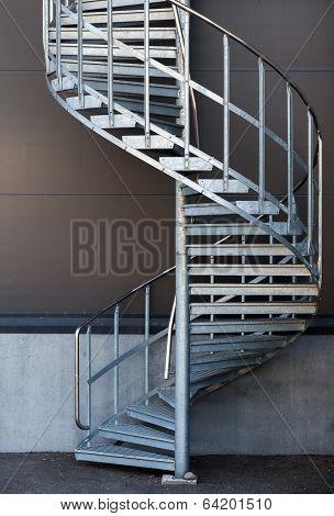 Modern metal spiral staircase above dark gray wall poster