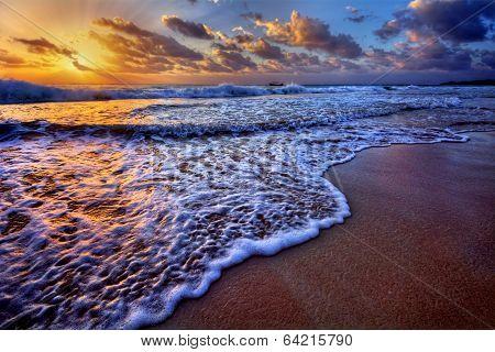 Serene beach destination sunrise with breaking wave crest and sea foam