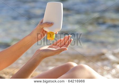 Woman Hands Putting Sunscreen From A Bottle On The Beach