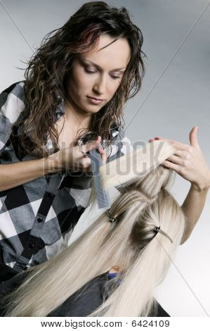 Serious Hairdresser Doing Hairstyle