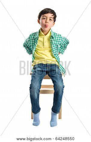 Boy Making A Mockery On Wooden Chair Over White