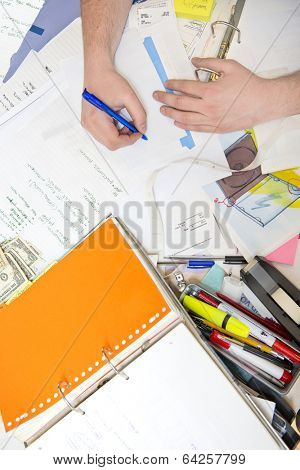 Messy desk, filled with documents, notes, pens and all sorts of office supplies, including a few dollar bills, with a hand taking notes on the back side of an enveloppe, seen from above.
