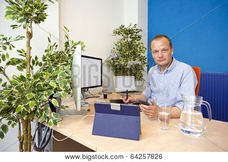 Man, taking a phone call in a paperless office, using various electronics, working in the cloud in an environmental friendly way
