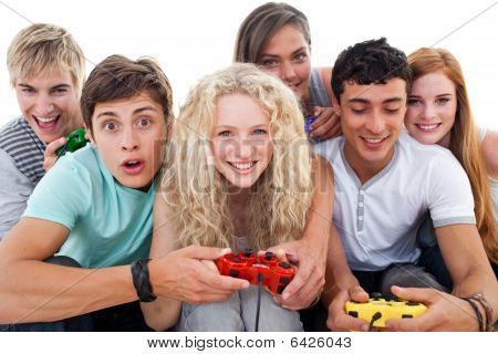 Excited Teenagers Playing Video Games In The Living-room