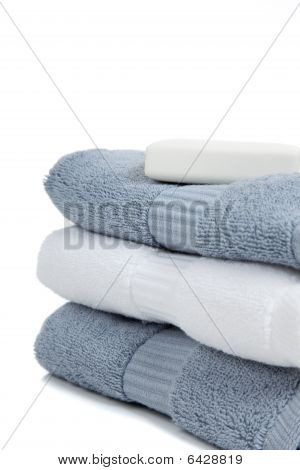Gray Blue And White Towels With A Bar Of Soap On White With Copy Space