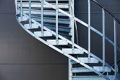 Fragmetn of modern metal spiral staircase above dark gray wall poster
