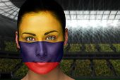 Composite image of beautiful colombia fan in face paint against vast football stadium with fans in yellow poster