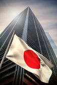 Japan national flag against low angle view of skyscraper poster