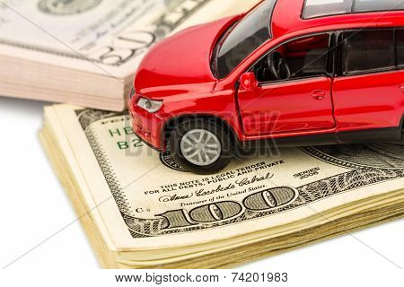 a car stands on dollar banknotes. costs for the purchase of automobiles, gasoline, insurance and other car costs