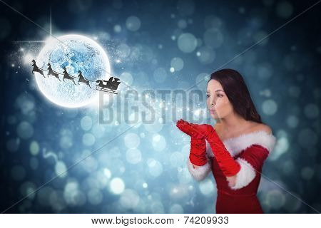 Pretty girl in santa outfit blowing against santa and his sleigh flying