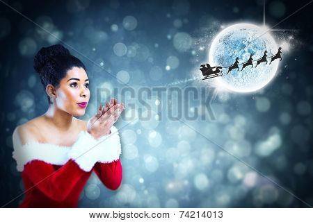 Pretty santa girl blowing over her hands against santa and his sleigh flying