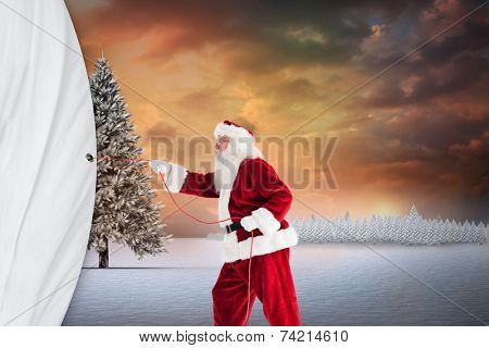 Santa pulls something with a rope against fir tree in snowy landscape poster