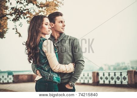 Beautiful young couple near river on autumn fogy day