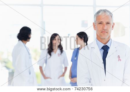 Mature doctor standing in the foreground wearing breast cancer awareness ribbon