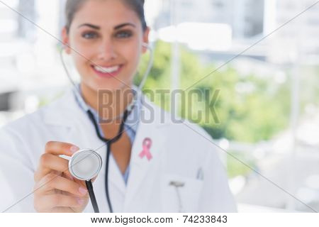 Pretty young doctor holding up stethoscope wearing breast cancer awareness ribbon