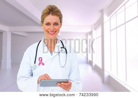 Blonde doctor using tablet pc against white room with windows