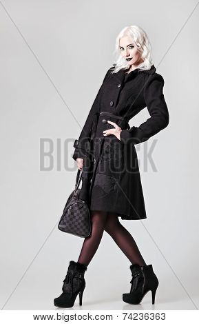 Studio Fashion Shot: A Beautiful Girl In Black Coat And Boots, With Bag In Hand