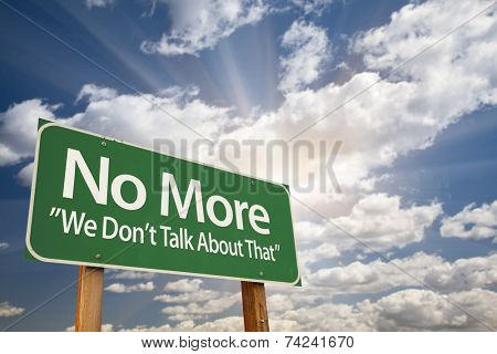 No More - We Don't Talk About That Green Road Sign with Dramatic Clouds and Sky.