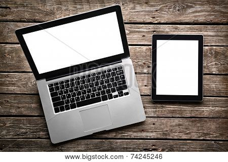 Open laptop with digital tablet. With isolated screen on old wooden desk.