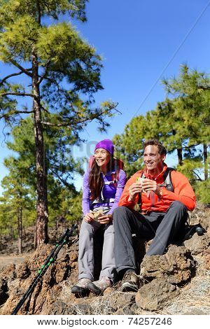 Hikers couple relaxing eating lunch sandwich. Hiking people living active lifestyle in mountain nature. Woman and man hiker sitting during hike on volcano Teide, Tenerife, Canary Islands, Spain.