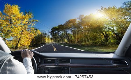 Hands on steering wheel of a car driving on an asphalt road