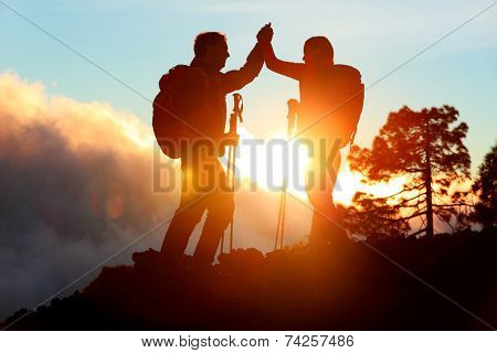 Hiking people reaching summit top giving high five at mountain top at sunset. Happy hiker couple silhouette. Success, achievement and accomplishment people poster
