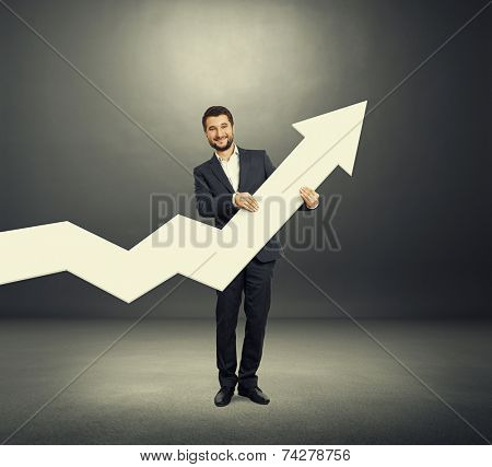 smiley businessman standing in the dark room and holding white pointer